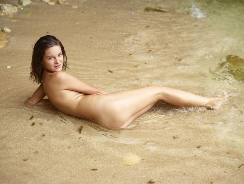 Брюнетка разлеглась без купальника на фоне залива