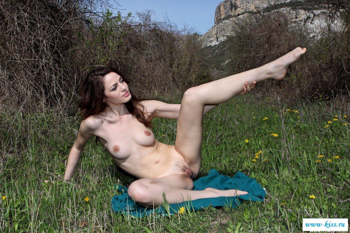Раздетая модель с темными волосами на коленках в траве