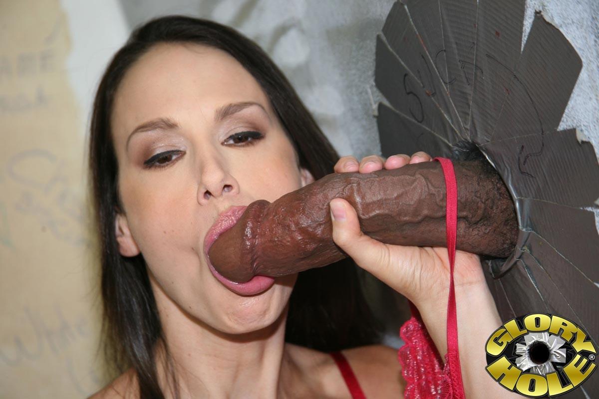 Проститутка сидя на унитазе хватается пальцами за крупные черные писюны у стены