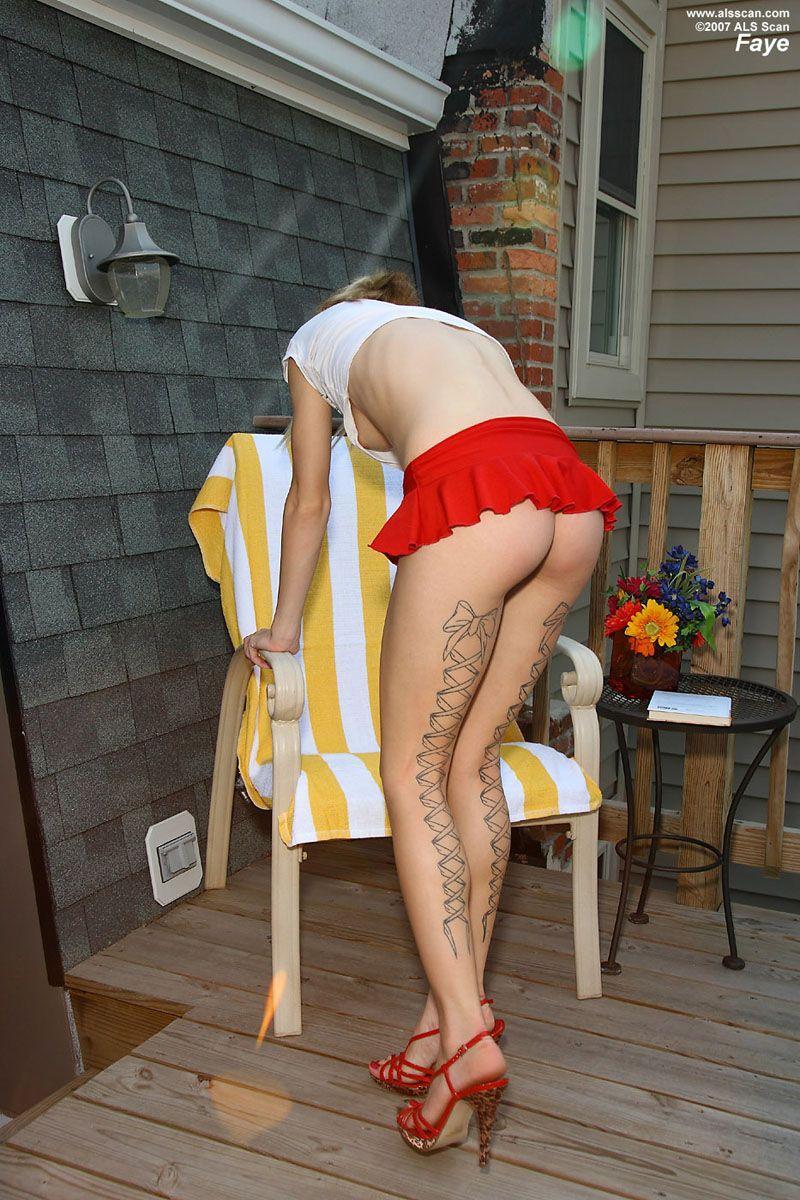 Модель со свелыми волосами в крохотной красной юбке Faye Runaway показывает свою розовую