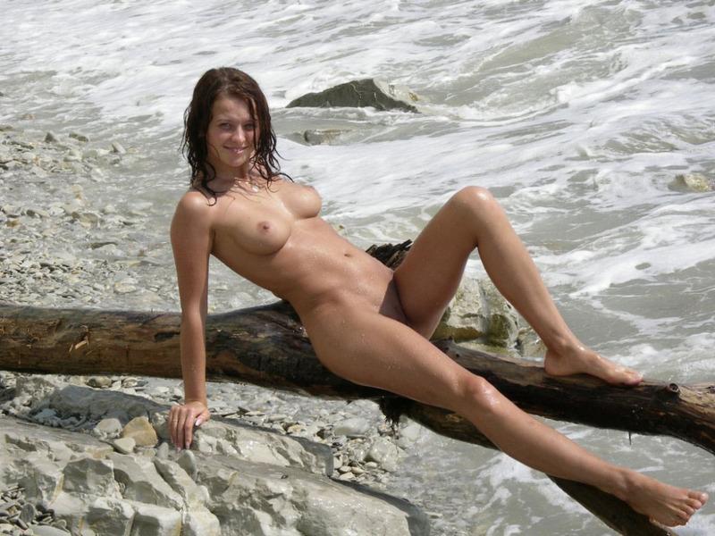 Голая темноволосая девка наслаждается брызгами морских волн на возбуждающее тело