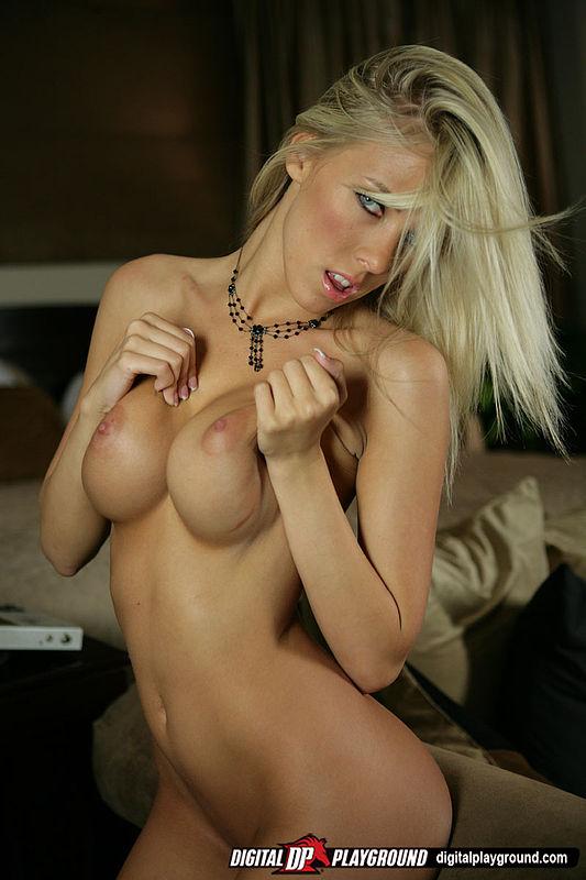 Светлая порноактриса светит гигантскими грудями и жопой возле софы с подушками