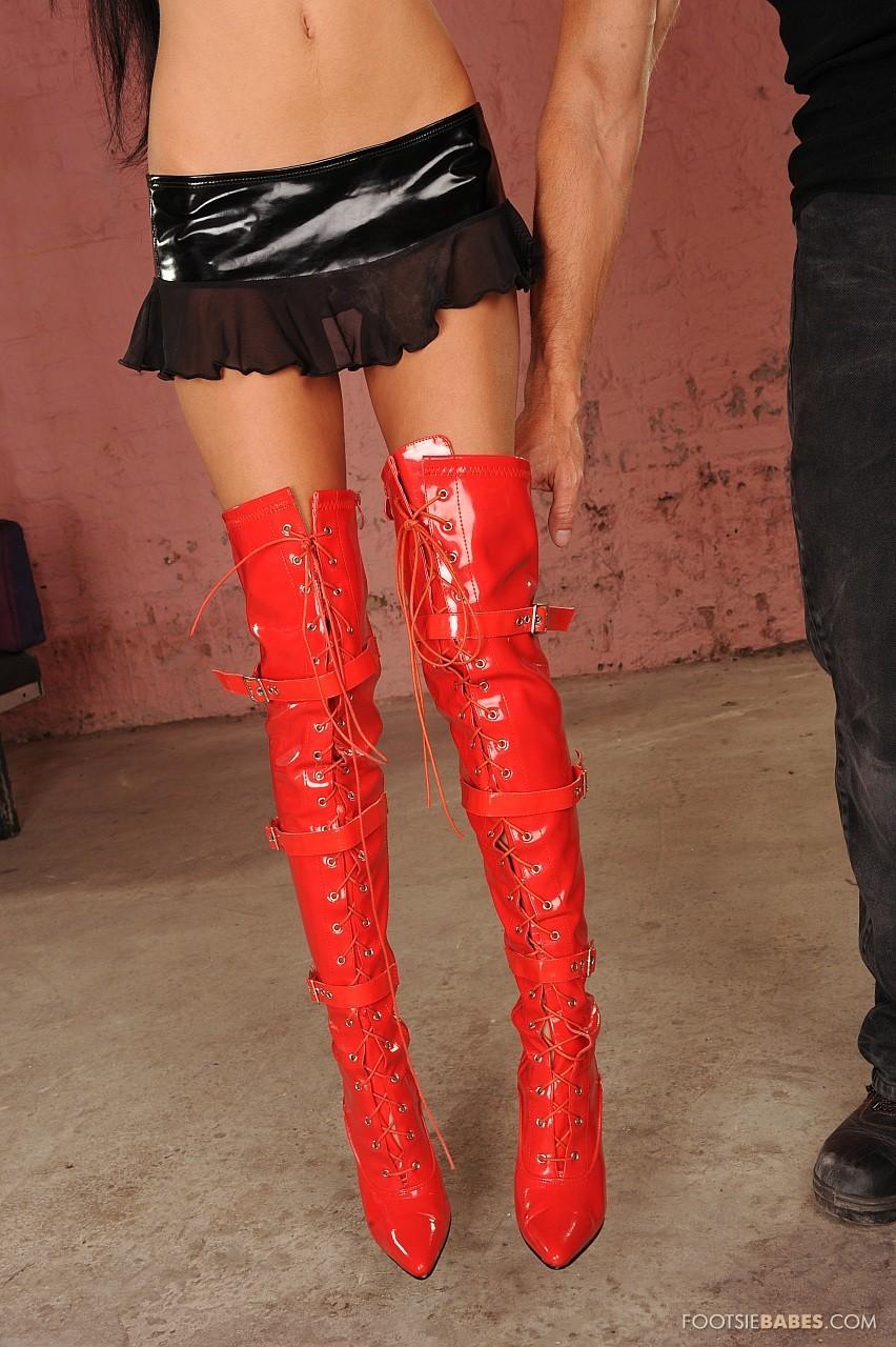 Сексапильная рабыня Sasha Rose стаскивает красную латексную юбке и узкие высокие сапожки, а затем подвергает мучениям свои дырки